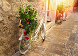 Stunning view of stoned paved street in old town on sunrise. Pots with flowers standing on vintage bicycles along a wall. Sun light on stone walls. Travel Montenegro