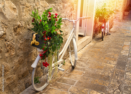 Fototapeta Stunning view of stoned paved street in old town on sunrise. Pots with flowers standing on vintage bicycles along a wall. Sun light on stone walls. Travel Montenegro