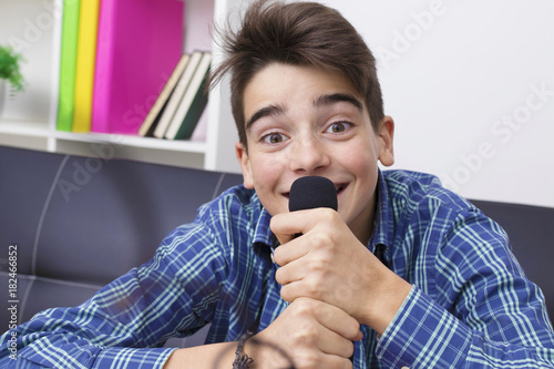 Fototapeta child, teenager or preteen singing with the microphone