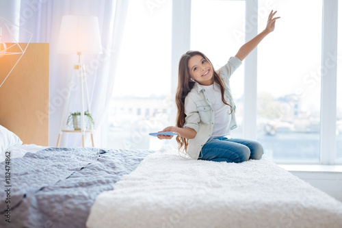 Fotobehang Muziek Flying in dreams. Kind little enthusiastic girl listening to music while holding a phone and bringing one hand up