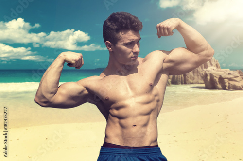 Attractive muscular man by the sea, shirtless looking at camera, standing in the Poster
