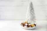 christmas tree from flocked wire and cookies like cinnamon stars and marzipan balls in a pottery bowl on a white painted wooden background with large copy space - 182479810