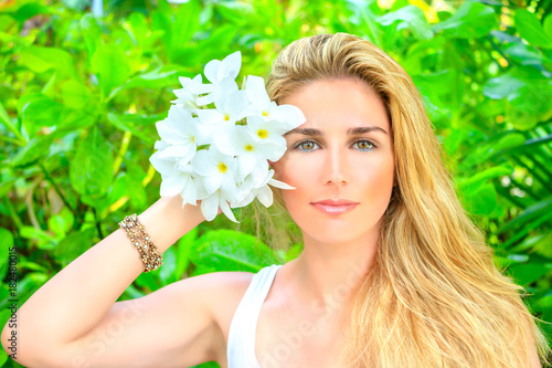 Leinwanddruck Bild Sweet blonde girl with Frangipani
