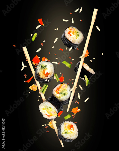 Keuken foto achterwand Sushi bar Pieces of sushi frozen in the air on black background