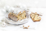 German Christmas cake, called criststollen with raisins and candied fruit on a white plate, decorated with bright Christmas balls and cinnamon stars on a white table, copy space - 182480827