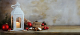 Christmas background, lantern with candle light, gifts, red balls, pine cones and cinnamon star cookies on a rustic wooden table against a vintage wall, panoramic banner format, copy space - 182481234