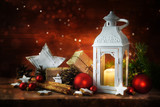 Christmas or Santa Claus gave table, candle lantern, gifts, red christmas ornaments, pine cones and cinnamon star cookies against rustic reddish wood, bokeh lights in the background, copy space - 182481849