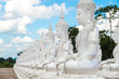 Cropped shot view of white Buddha statue sitting in a rows.