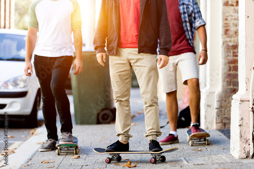 Teenage friends walking at the street with skateboards Poster