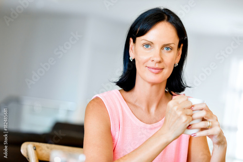 Happy woman with cup of tea or coffee at home Poster