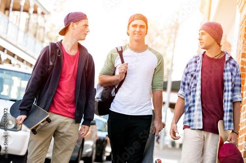 Wall mural Teenage friends walking at the street