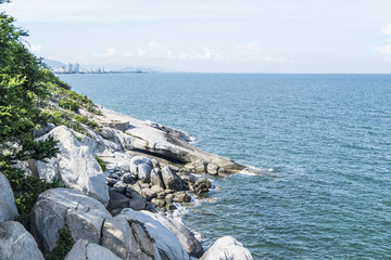Rock of reef on mountain with blue sea and cityscape