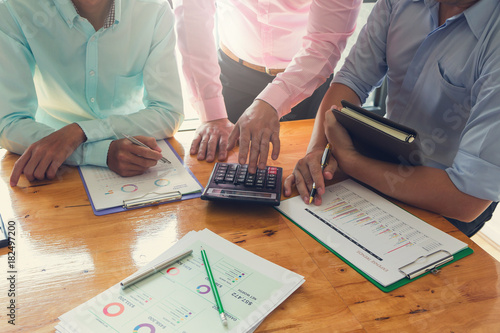 Fototapeta Business and finance concept of office working,Teamwork of Businessmen using calculator to discussing analysis Chart
