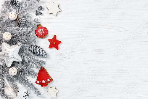 silver christmas tree branches with lights, star and gingerbread cookies on white wooden background flat view