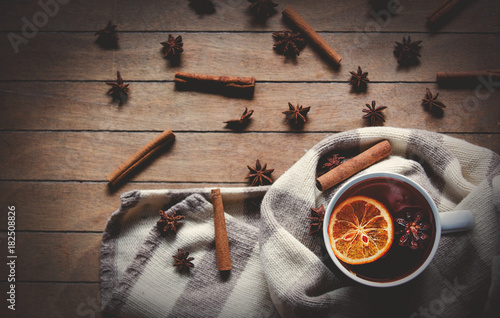 Cup of tea with lemon and scarf near cinnamon nad star anise