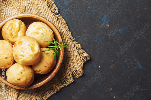 Tasty buns with rosemary, rustic style, black background, top view