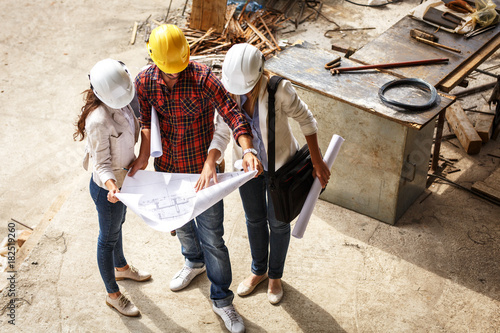 Two female  architects discuss with head engineer about blueprints of construction site.