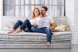 A beautiful young couple sitting on the sofa and cuddling.