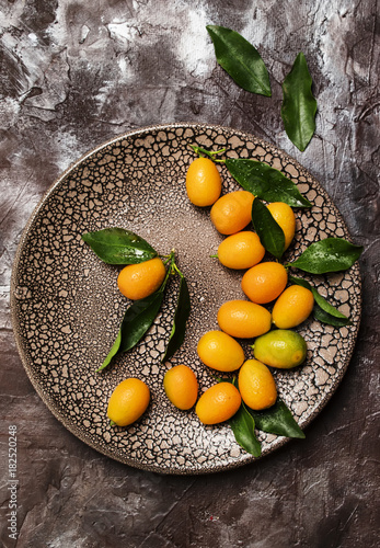 Poster Fresh kumquat with leaves on a plate, brown background, top view