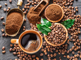 Roasted coffee beans, ground coffee and cup of coffee on wooden table. - 182525899