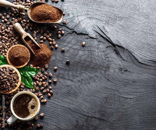 Wall mural Roasted coffee beans  and ground coffee on wooden table. Top view.