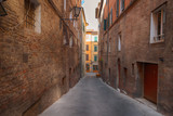 Beautiful medieval narrow street in the spring, Siena, Italy. Historic centre of Siena has been declared by UNESCO a World Heritage Site.