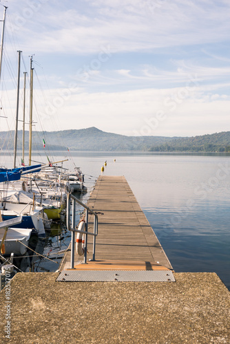 Sail boats dock at wooden floating tourist pier in sunny summer morning Poster