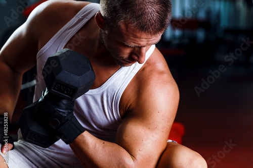 Fototapeta Young man exercising with weight in the gym.