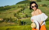 View of a girl in dress in Tuscany hills, Italy