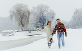 Full-length portrait of the beautiful couple holding hands while happily walking along the village covered with snow during the snowfall. - 182554022