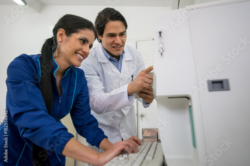 Fototapeta Doctor and assistant taking a look at an xray of a pet on screen both looking very happy