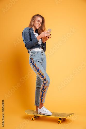 Aluminium Skateboard Full length portrait of a smiling young girl skateboarder