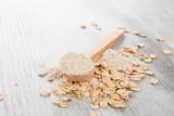 Oat flour in wooden spoon. - 182558885