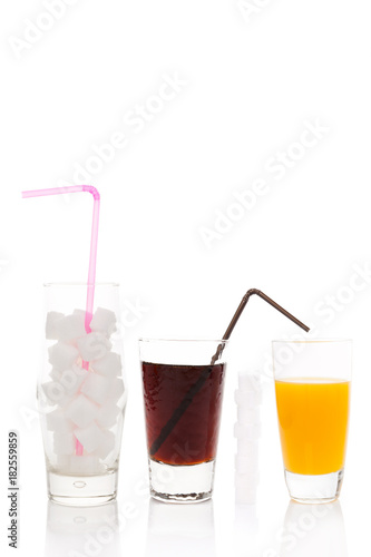 Cola, sugar cubes and orange juice in glass.