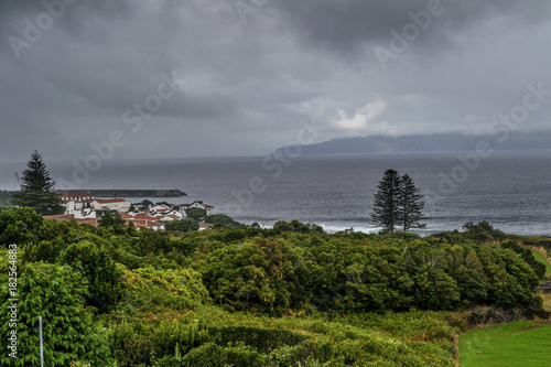 Keuken foto achterwand Donkergrijs small fishing village and green fields on the coast of Pico after sunset in the Azores
