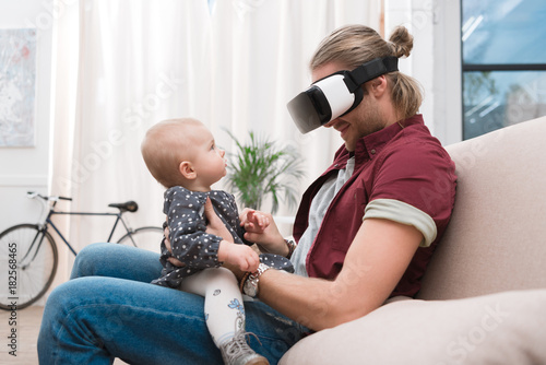 Fototapeta smiling father sitting with his little daughter and using Virtual reality headset