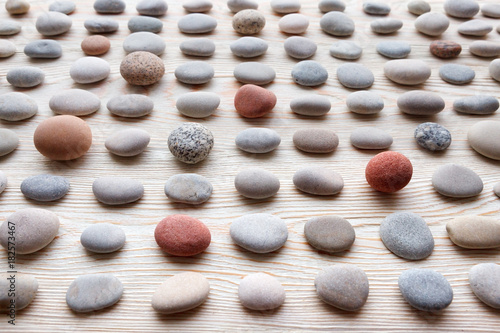 Foto op Canvas Zen pattern of colored pebbles on white wooden background