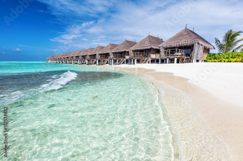 Papiers peints Tropical plage Water villas in a row by the seashore on Maldives Tropical resort