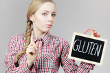 Woman holding board with gluten sign - 182578895