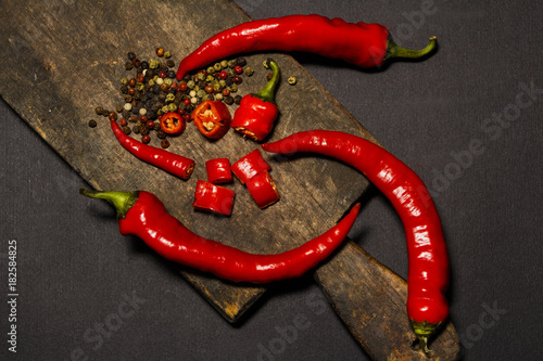 Tuinposter Hot chili peppers Red hot chili pepper corns and pods on dark background, top view.