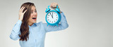 Businesswoman dressed in blue office shirt holding alarm clock.