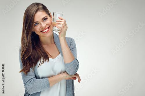 Młoda uśmiechnięta kobieta trzyma wodnego szkło. Odosobniony pracowniany portret