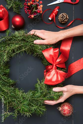 florist hands making Christmas wreath