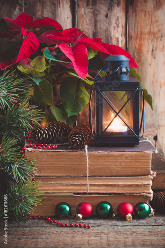 Christmas postcard with Poinsettia on the old books with fir tree, cones and toys balls and burning lantern