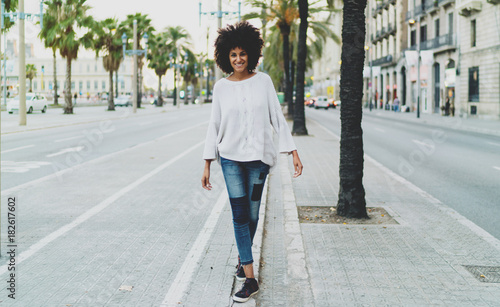 Full length portrait of smiling student female in casual clothing while standing on urban setting copy space area for advertising, young woman with curly hair enjoying city walking. - 182617602