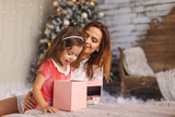 Happy mom with kid looking inside of magic Christmas gift box - 182627030