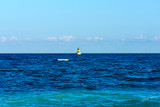 Seascape. Blue sea and sky. In the background a small lighthouse. - 182629620