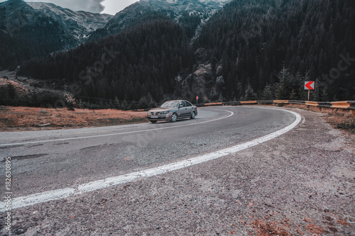 Fotobehang Grijze traf. Car on a beautiful mountains road, sport car on a highway, amazing sky with clouds, peak