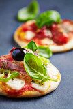 Mini pizza topped with ham, black olives and basil - 182631235