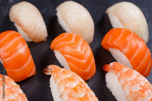 Foto op Canvas Sushi bar Nigiri sushi with salmon,grouper and prawn, served on black stone slate. Delicious traditional Japanese food, tasty seafood, restaurant concept, food background